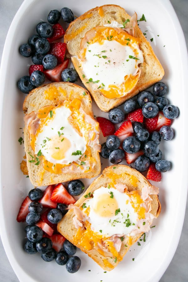 Crispy Ham and melty Cheese Egg in a Hole with blueberries and strawberries on a white platter.