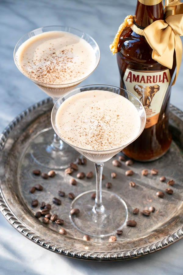 Espresso Martini in a coup glass with festive twinkle lights and coffee beans and a bottle of Amarula liqueur in background.
