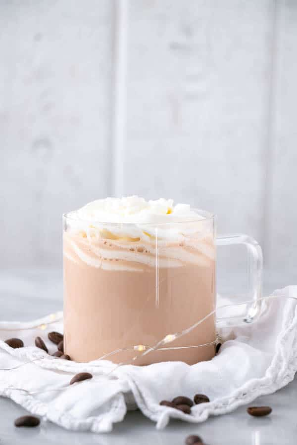 Creamy and decadent Hot White Russian topped with whipped cream in a clear glass mug.