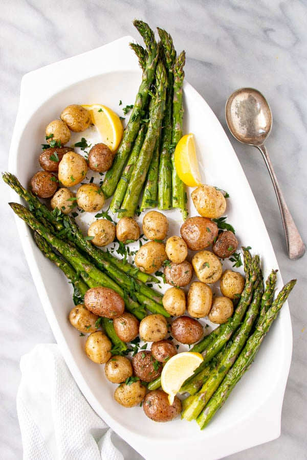 Roasted Potato and Asparagus with lemon slices on a white serving plate.