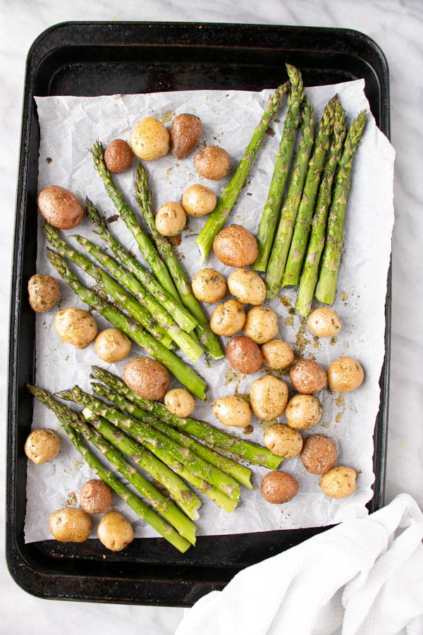 Roasted Potato and Asparagus with lemon slices on a baking sheet.