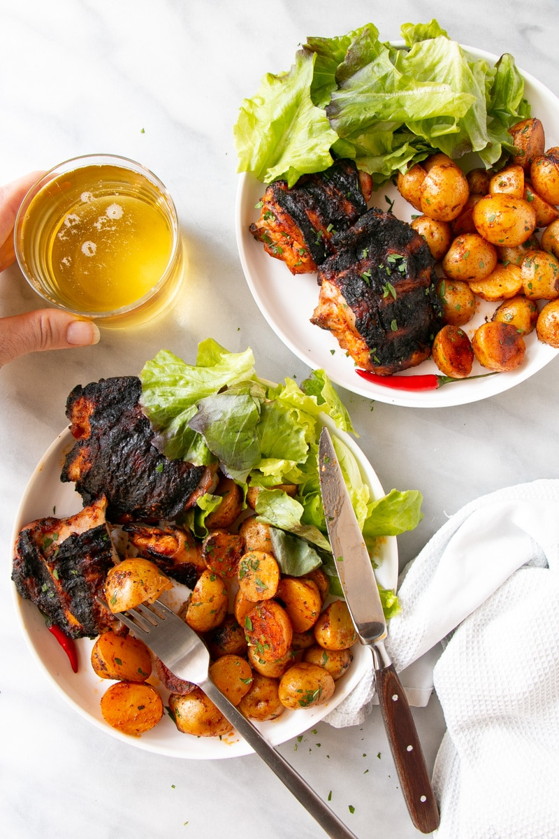 Grilled Peri Peri Chicken and Potatoes with a leafy green salad on a white plate.