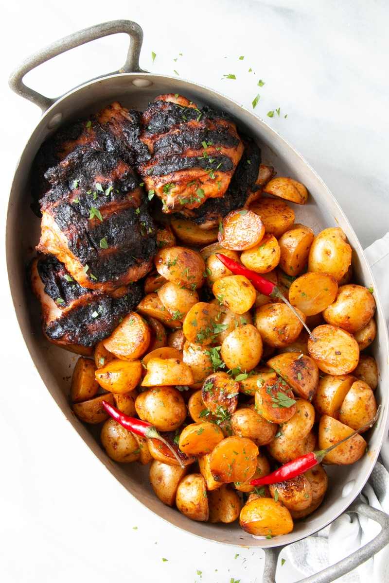 Peri Peri Grilled Chicken and Potatoes in an oval shaped metal dish.