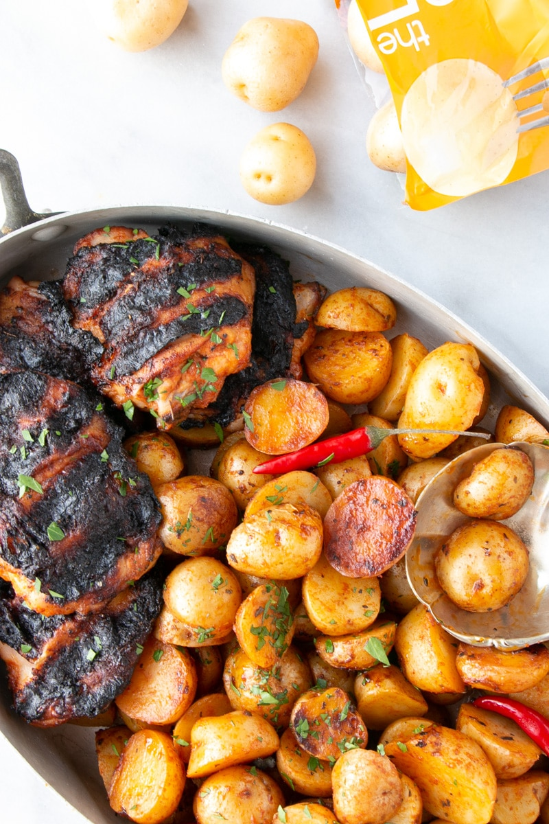 Grilled Peri Peri Chicken and Potatoes up close with some potatoes in a scalloped shaped serving spoon.