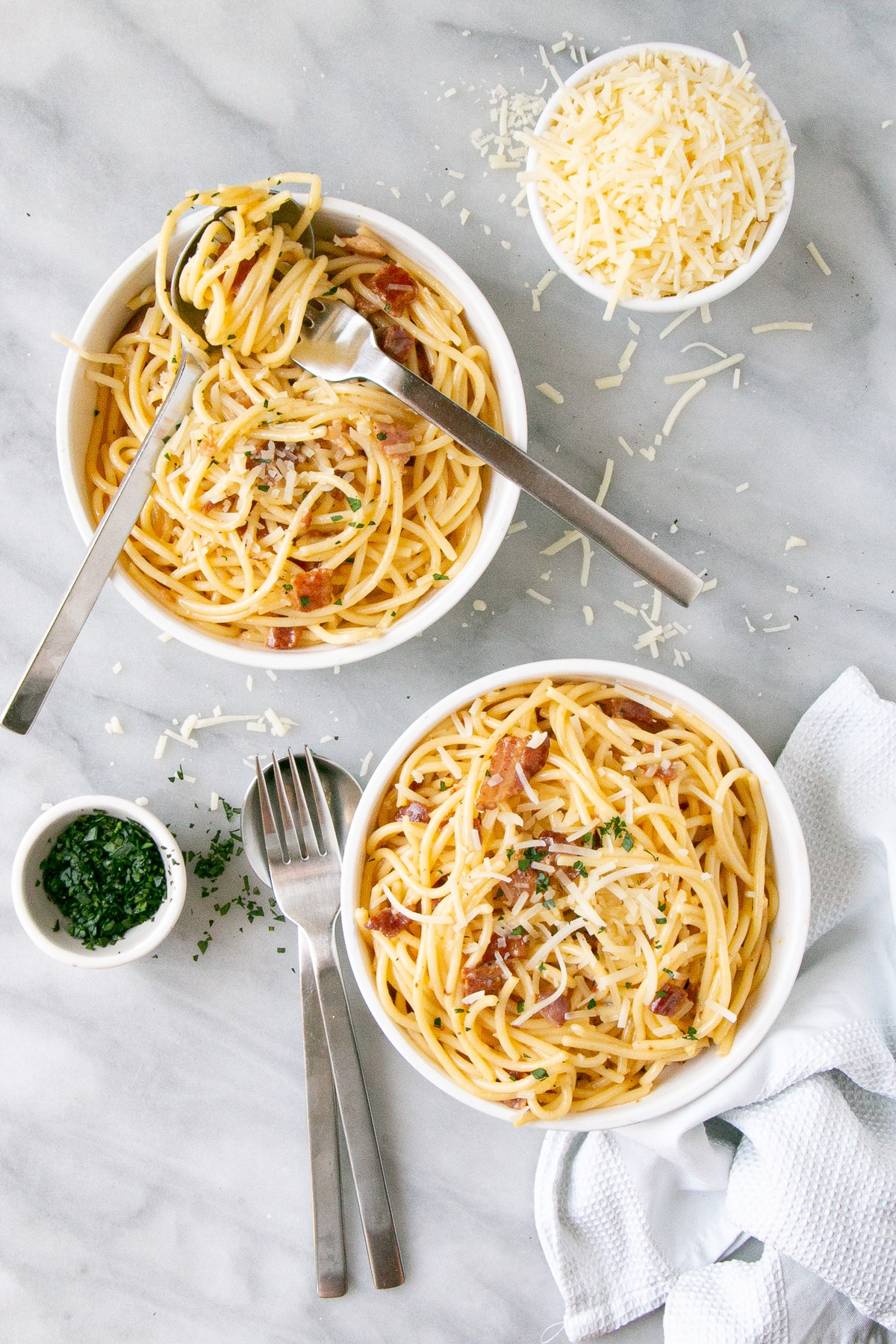 The best Spaghetti Carbonara in a white bowl with parmesan shreds and chopped parsley in small bowls and sprinkled on top.