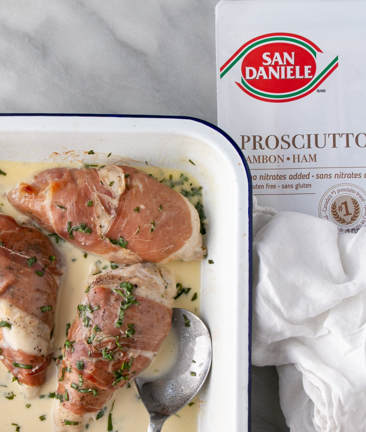 Prosciutto-Wrapped Chicken in a creamy mustard sauce with a scattering of fresh basil on top and the prosciutto packaging beside baking tray.