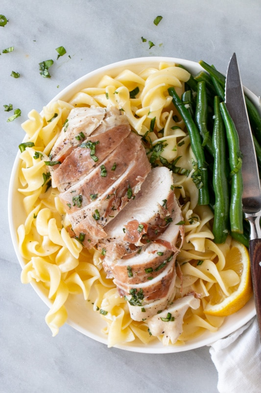 Prosciutto-Wrapped Chicken on top of a bed of broad egg noodles and a side of green beans.